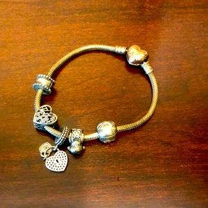 Pandora bracelet with four charms and the one that comes with it.